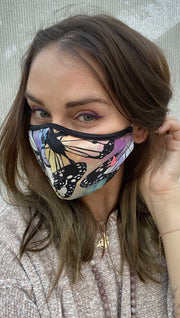Slightly turned left side view of model wearing a colorful butterfly themed mask