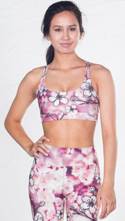 front view of model wearing cherry blossom inspired printed sports bra
