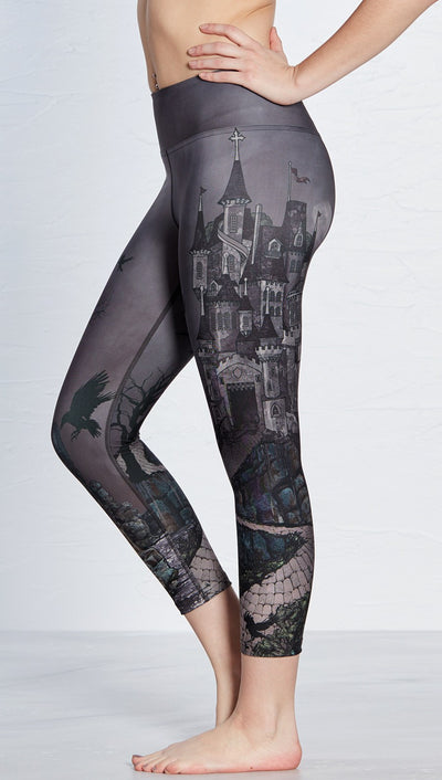 closeup left side view of model wearing castle design printed capri leggings