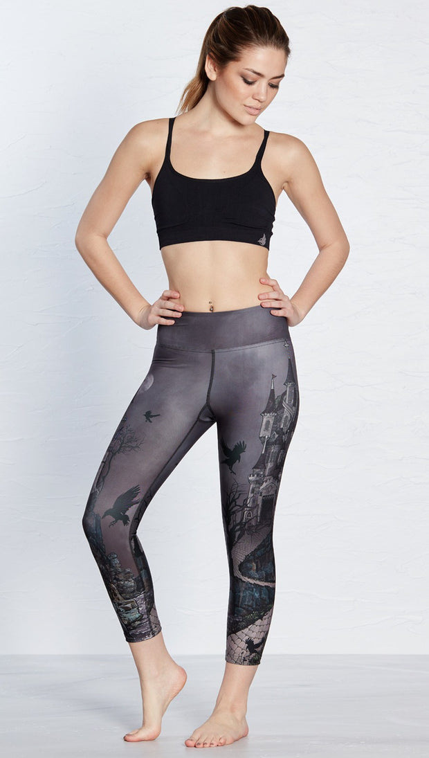 front view of model wearing castle design printed capri leggings and sports top