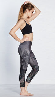 right side view of model wearing castle design printed capri leggings and sports top