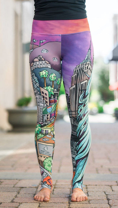 closeup front view of model wearing full length printed leggings with various cities design