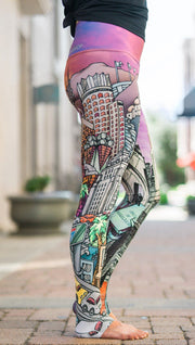 closeup right side view of model wearing full length printed leggings with various cities design