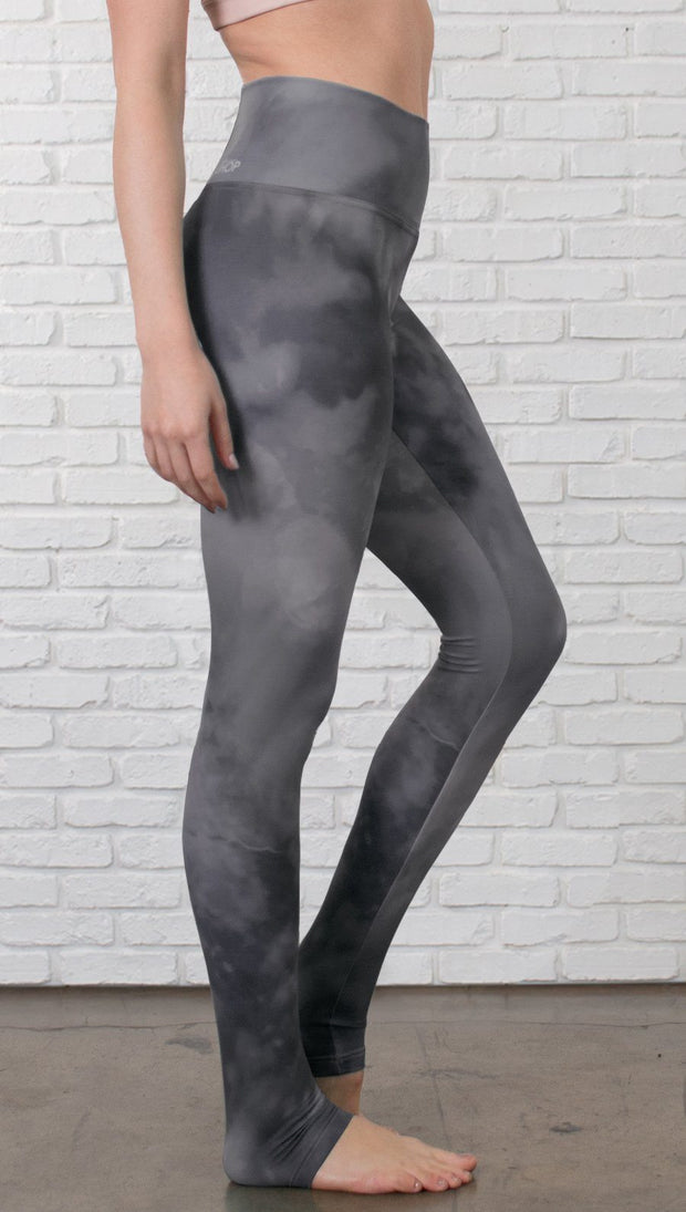 closeup right side view of model wearing grey cloud watercolor printed full length leggings