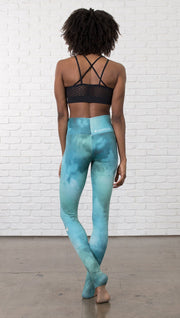 back view of model wearing water / ocean themed printed full length leggings with black sports top
