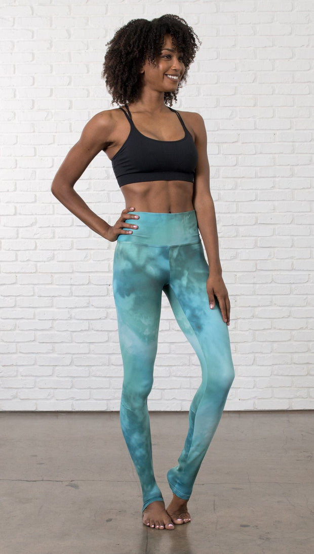 front view of model wearing water / ocean themed printed full length leggings with black sports top