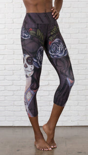 close up front view of model wearing sugar skull themed printed capri leggings