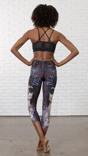 back view of model wearing sugar skull themed printed capri leggings