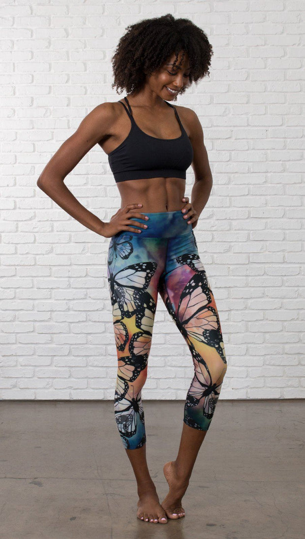 slightly turned front view of model wearing colorful butterfly themed printed capri triathlon leggings