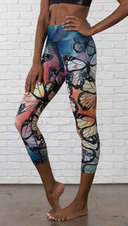 closeup left side view of model wearing colorful butterfly themed printed capri triathlon leggings