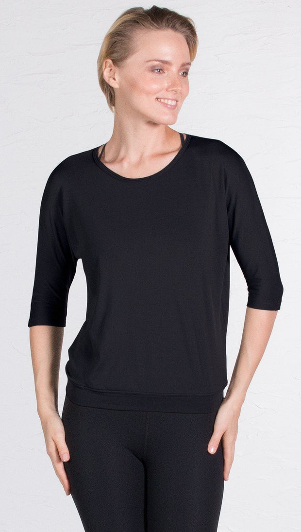 closeup front view of model wearing 3/4 Sleeve black Performance Top with Open Back and Loose / Athleisure Fit