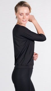 closeup right side view of model wearing 3/4 black Sleeve Performance Top with Open Back and Loose / Athleisure Fit
