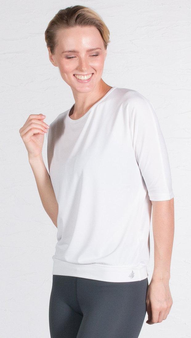 closeup front view of model wearing 3/4 Sleeve white Performance Top with Open Back and Loose / Athleisure Fit