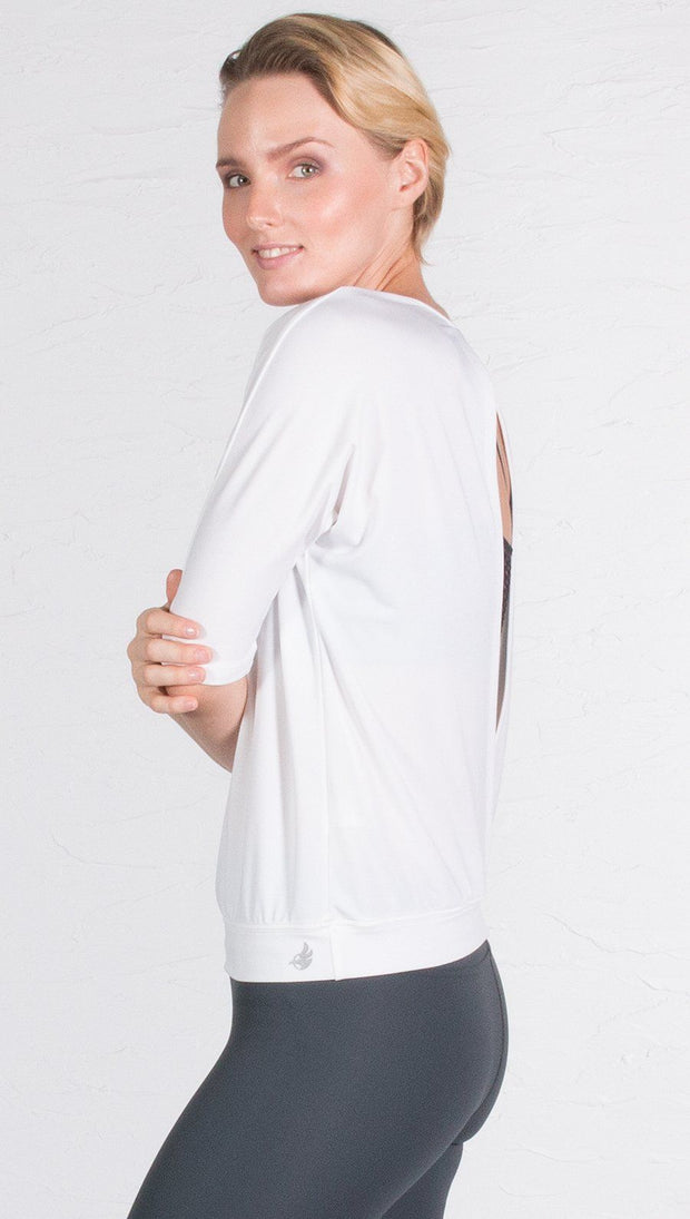 closeup left side view of model wearing 3/4 Sleeve white Performance Top with Open Back and Loose / Athleisure Fit