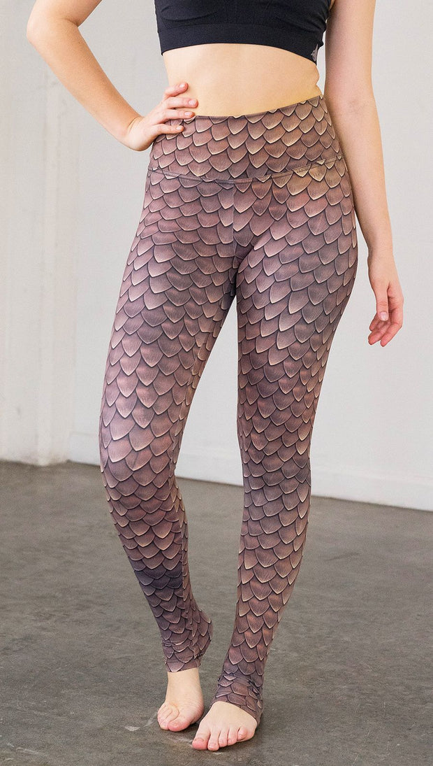 Front view of model wearing brown dragon scale printed full length leggings