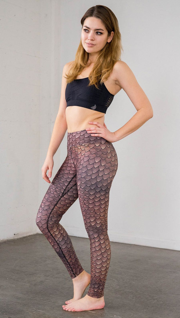 Left side view of model wearing brown dragon scale printed full length leggings