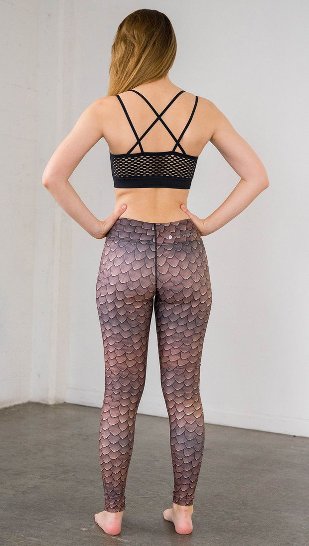 Back view of model wearing brown dragon scale printed full length leggings