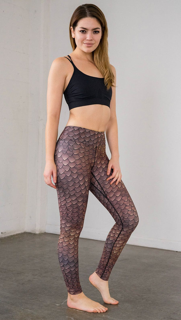 Right side view of model wearing brown dragon scale printed full length leggings