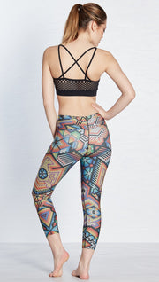 back view of model wearing beaded themed printed capri leggings with eagle motif