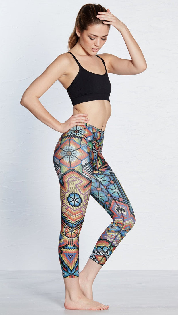 right side view of model wearing beaded themed printed capri leggings with eagle motif