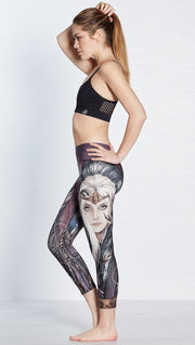 left side view of model wearing capri leggings with printed elf design