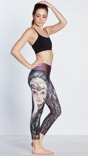 right side view of model wearing capri leggings with printed elf design