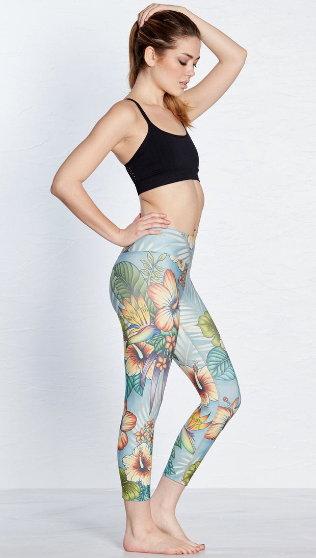 right side view of model wearing printed capri leggings with tropical floral design and blue background