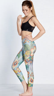 left side view of model wearing printed capri leggings with tropical floral design and blue background