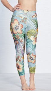 front view of model wearing printed capri leggings with tropical floral design and blue background