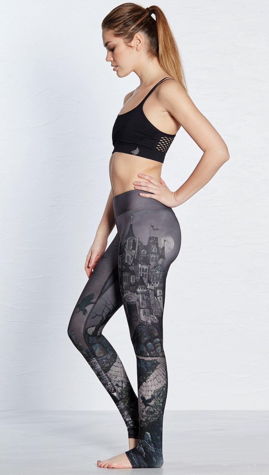 closeup left side view of model wearing castle design printed full length leggings