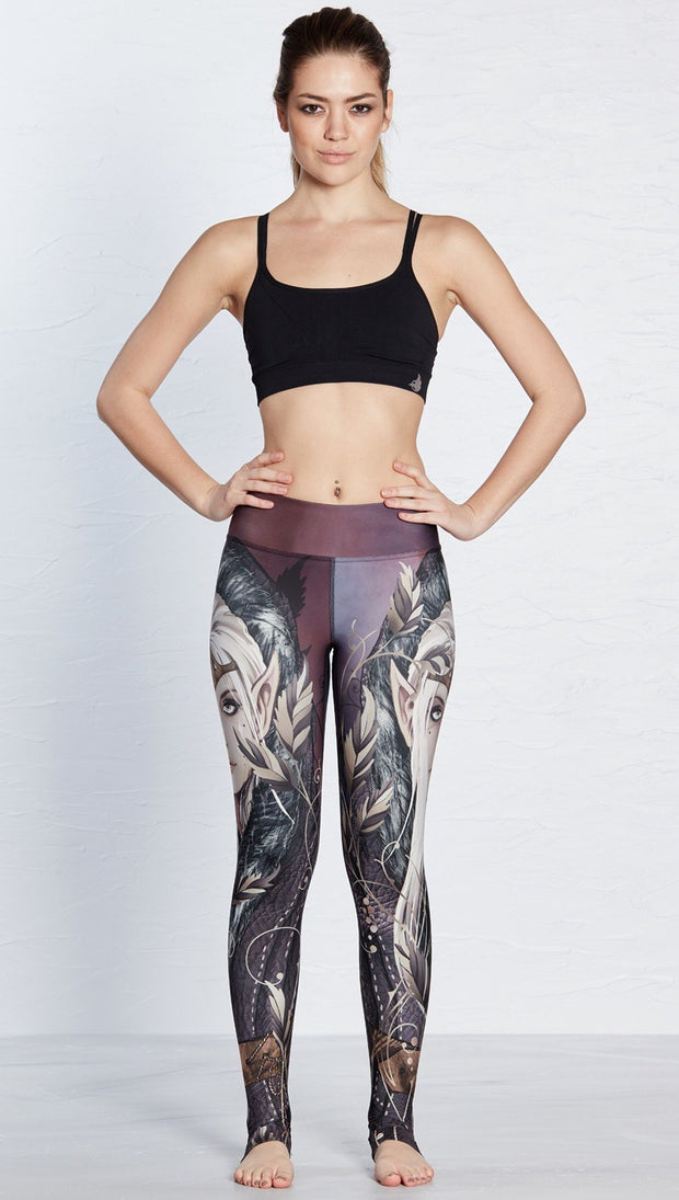 front view of model wearing full length leggings with printed elf design