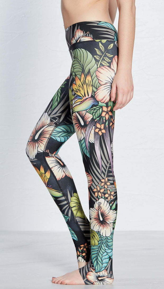 close up left side view of model wearing printed full length leggings with tropical floral design and black background
