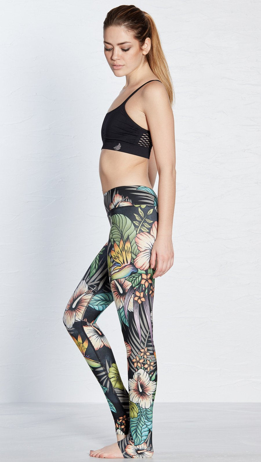 close up side view of  printed full length leggings with tropical floral design and black background