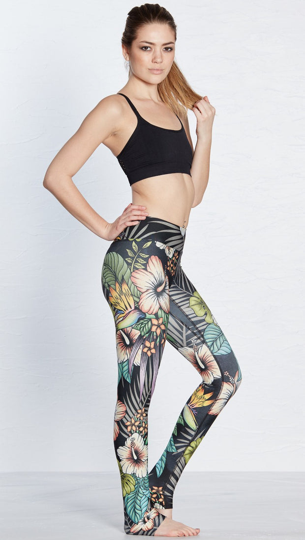 right side view of model wearing printed full length leggings with tropical floral design and black background
