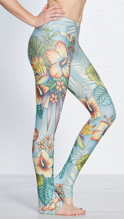 close up side view of  printed full length leggings with tropical floral design and blue background