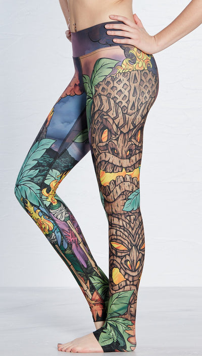 close up side view of island tiki themed printed full length leggings