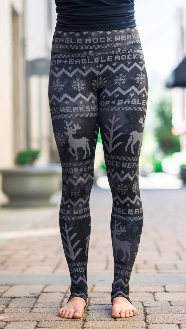 closeup front view of model wearing holiday themed full length leggings with reindeer and pine tree faux knit design