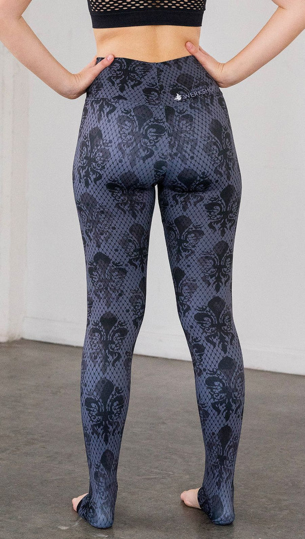 Back view of model wearing navy blue fleur de li pattern full length leggings