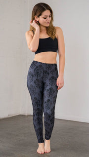 Front view of model wearing navy blue fleur de li pattern full length leggings