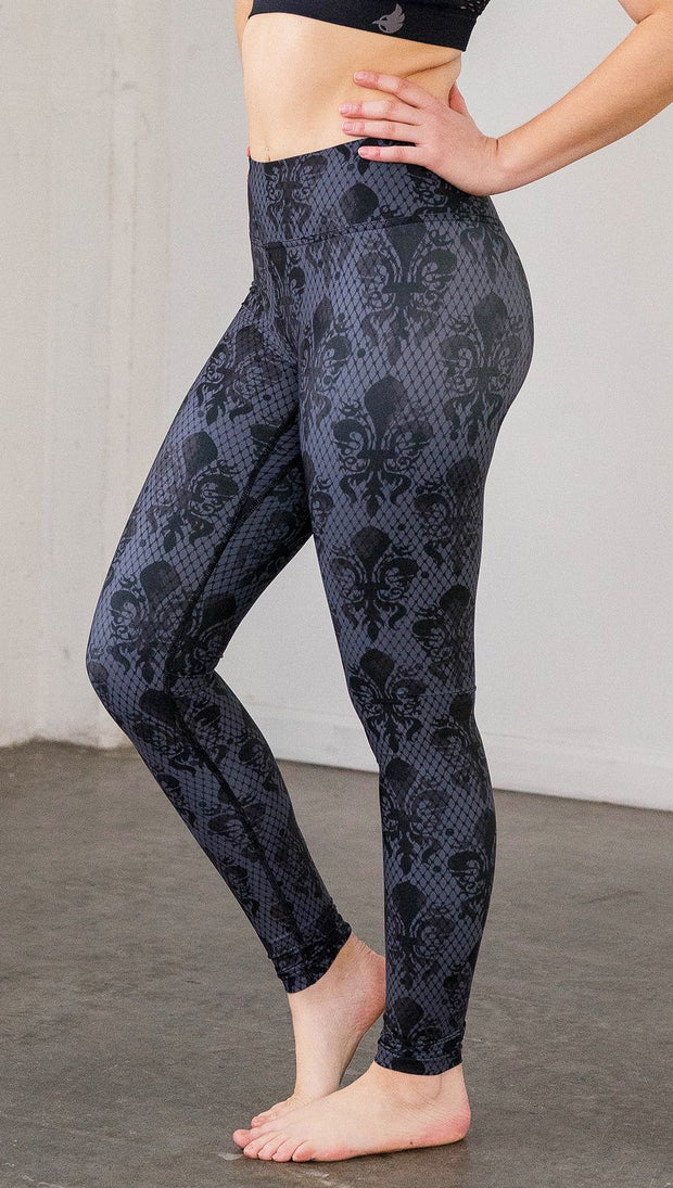 Left side view of model wearing navy blue fleur de li pattern full length leggings