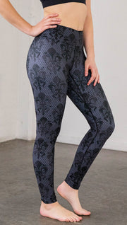 Right side view of model wearing navy blue fleur de li pattern full length leggings