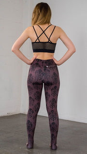 Back view of model wearing oxblood red fleur de li pattern full length leggings