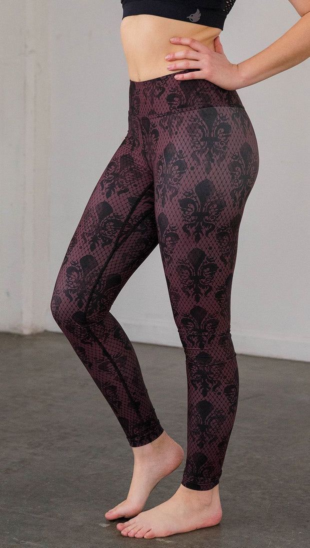 Left side view of model wearing oxblood red fleur de li pattern full length leggings