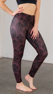 Right side view of model wearing oxblood red fleur de li pattern full length leggings