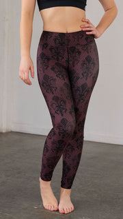Front view of model wearing oxblood red fleur de li pattern full length leggings