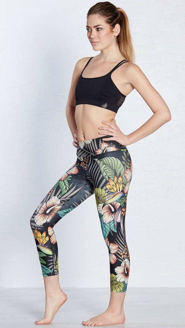 left side view of model wearing printed capri leggings with tropical floral design and black background