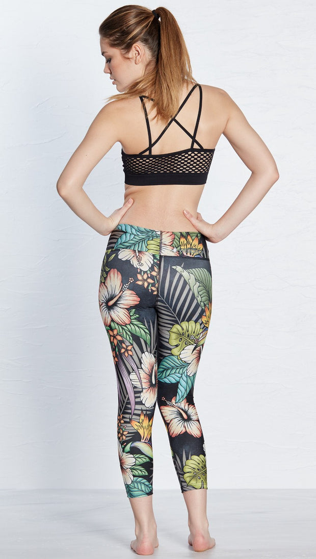 back view of model wearing printed capri leggings with tropical floral design and black background