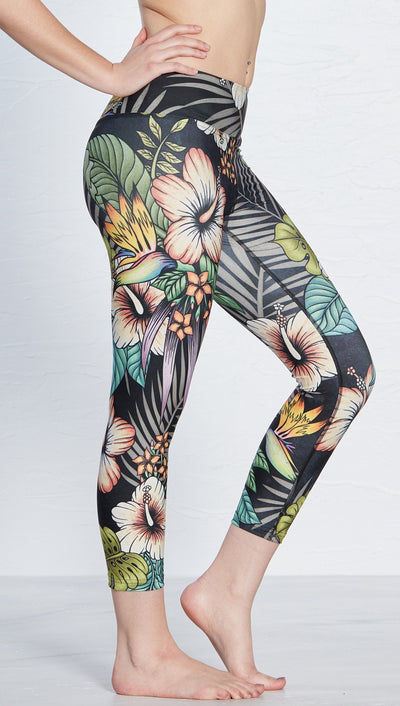 close up right side view of model wearing printed capri leggings with tropical floral design and black background