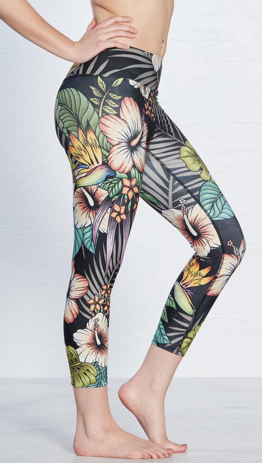 ffcb2c2b2738 close up side view of printed capri leggings with tropical floral design  and black background