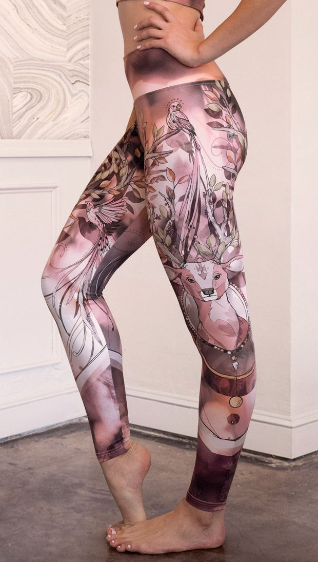 Left side view of model wearing full length leggings with a deer on it. They are a purple and orange color with tree branches as the antlers and birds on the antlers